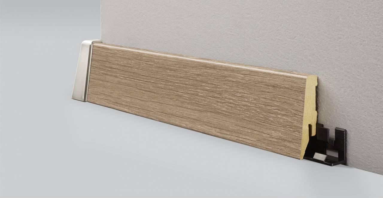 MDF дървесен подов перваз 8634 с кабелен канал и височина 58 мм е подходящ за ламиниран паркет в бежово-кафяв цвят.